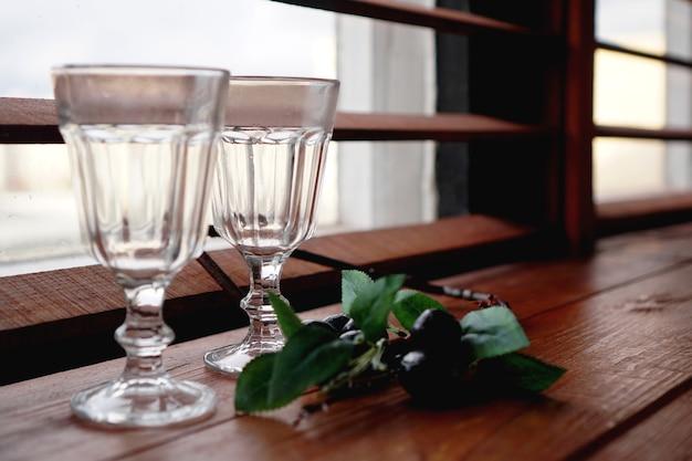 Finestra con un davanzale in legno accogliente - bicchieri vuoti e decorazioni floreali