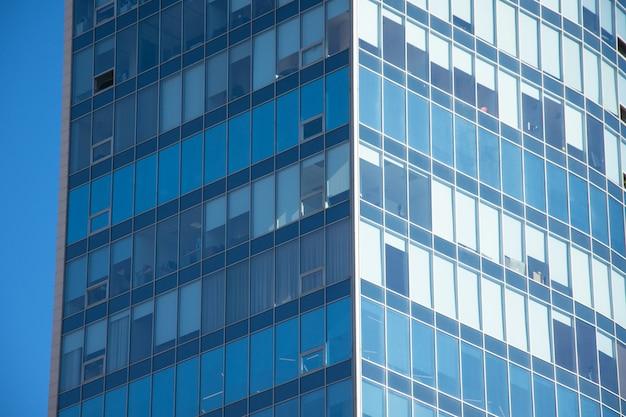 Edificio per uffici ad angolo di vetro di windows per lo sfondo.