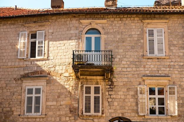 Finestre con persiane su una vecchia casa in pietra, vecchia architettura.