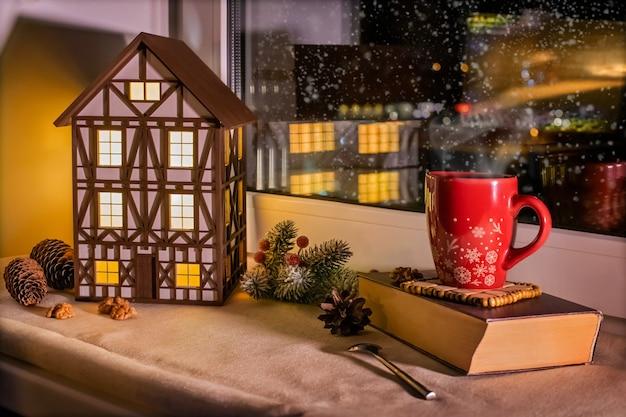 Sul davanzale della finestra c'è la luce notturna della casa a graticcio e la tazza rossa di natale tra le decorazioni natalizie