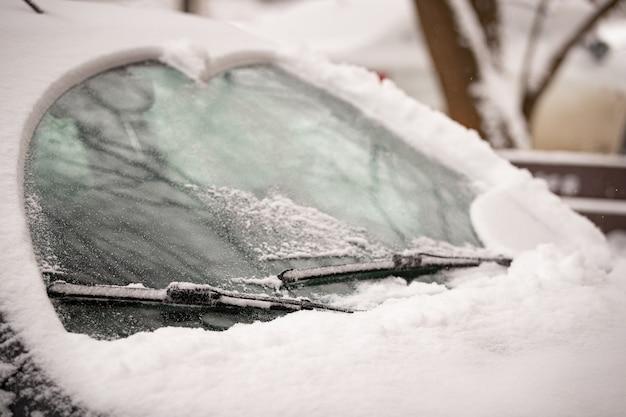 Le spazzole del tergicristallo puliscono il vetro ghiacciato dell'auto dalla neve in una giornata invernale di neve per una guida sicura