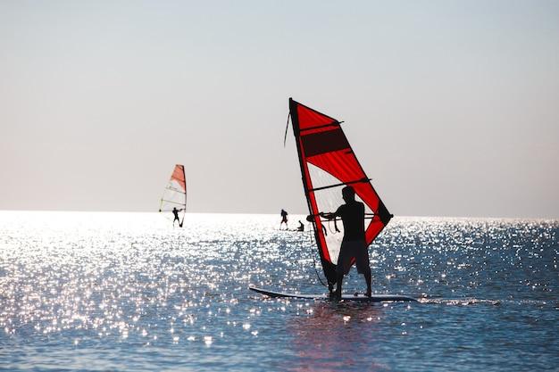 Windsurf in mare durante il tramonto, stile di vita attivo.