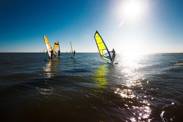 Silhouette di windsurf su uno sfondo al tramonto, stile di vita attivo, sport acquatici