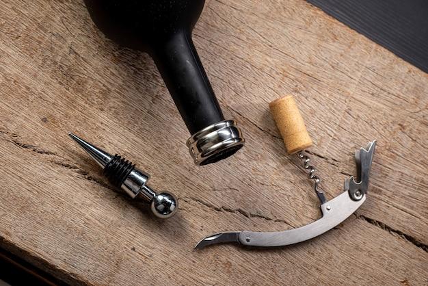 Kit accessori vino, con cavatappi, anello e tappo per bottiglia di vino, visto dall'alto su legno rustico.