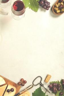 Set di antipasti di vino: selezione di formaggi francesi, uva e noci su concretebackground
