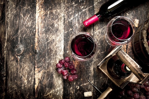 Sfondo di vino. vino rosso con bicchieri con uva. su uno sfondo di legno.