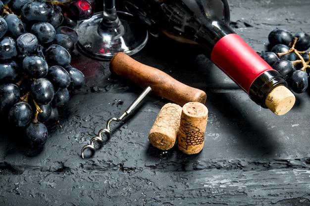 Sfondo di vino. vino rosso con uva e cavatappi. su uno sfondo nero rustico.