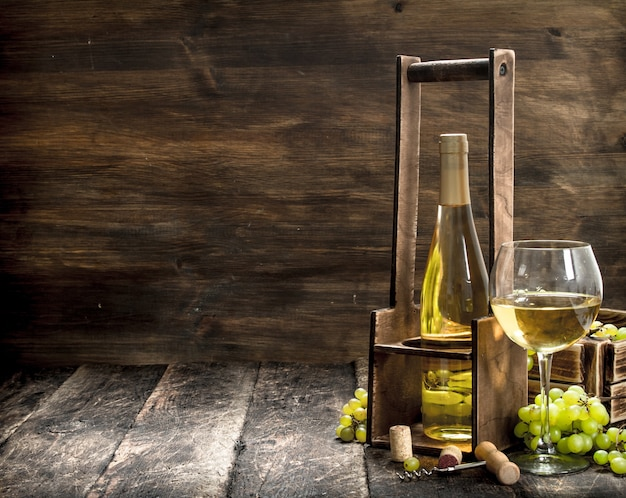 Sfondo di vino vino bianco su un supporto con rami di uve fresche su uno sfondo di legno
