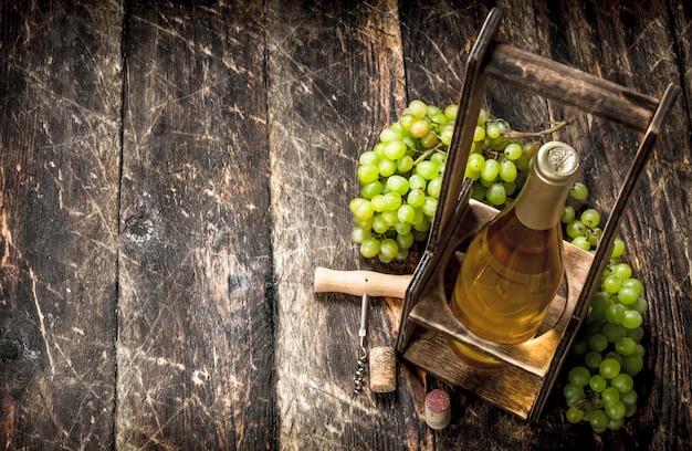 Sfondo di vino. vino bianco su una bancarella con rami di uva fresca. su uno sfondo di legno.