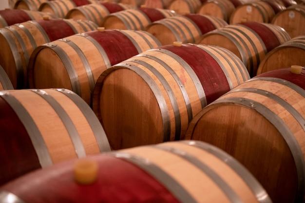Botti di vino accatastate nella vecchia cantina della cantina. (messa a fuoco selettiva)