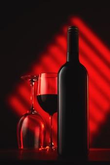 Bottiglia di vino e bicchieri al buio