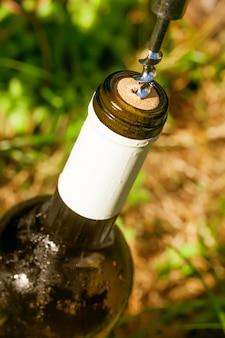 Apertura della bottiglia di vino avvitando un tappo di sughero
