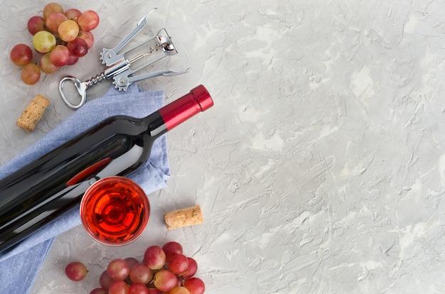 Bottiglia di vino, bicchiere di vino, grappoli d'uva rosa e cavatappi metallico su sfondo grigio strutturato. disposizione piatta. vista dall'alto. copia spazio.