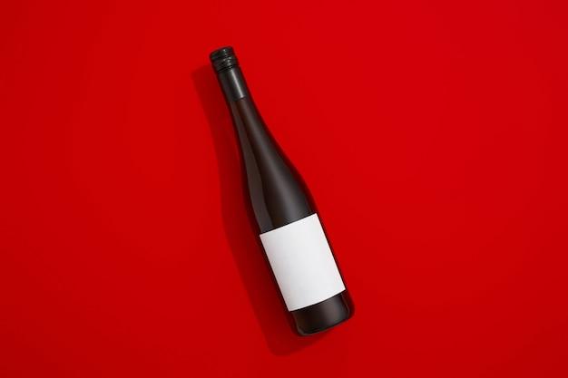 Bottiglia di vino con vino rosso etichetta vuota su sfondo colorato con spazio copia