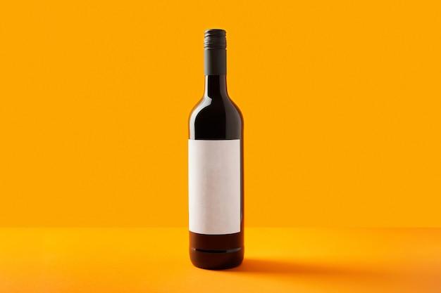 Bottiglia di vino con vino rosso etichetta vuota su sfondo creativo con spazio copia