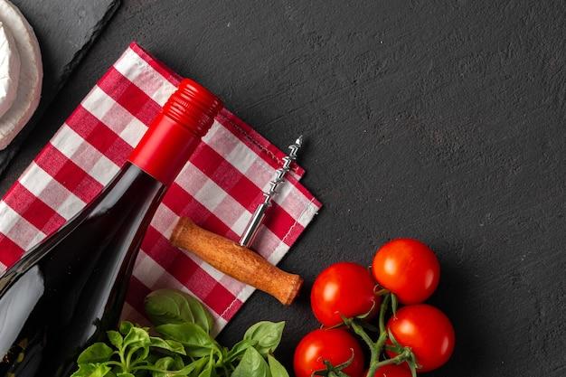 Bottiglia di vino con vite di sughero e pomodorini su sfondo nero