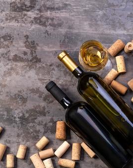 Bottiglie di vino e tappi di sughero sul tavolo scuro, vista dall'alto