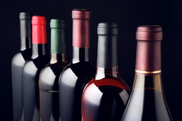 Bottiglie di vino in fila sul nero