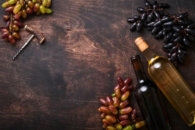 Bottiglie di vino con uva e bicchieri di vino sul vecchio fondo della tavola in legno scuro con spazio per le copie. vino rosso con un tralcio di vite. composizione del vino su fondo rustico. modello.