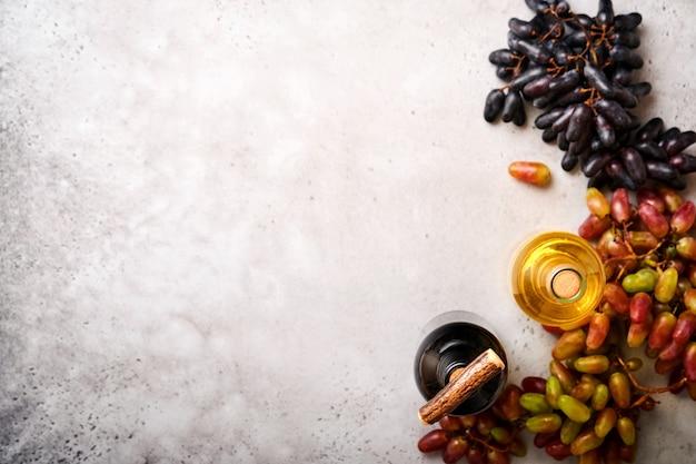 Bottiglie di vino con uva e bicchieri di vino sul vecchio sfondo grigio tavolo in cemento con spazio copia. vino rosso con un tralcio di vite. composizione del vino su fondo rustico. modello.