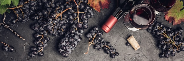 Composizione del vino su fondo rustico scuro, piatto laici