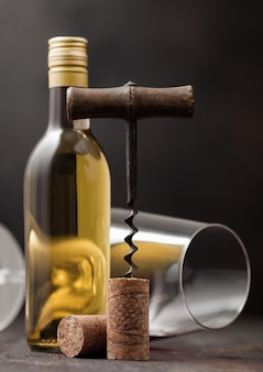 Sughero del vino con cavatappi vintage in cima su sfondo di legno con vetro e bottiglia di vino bianco