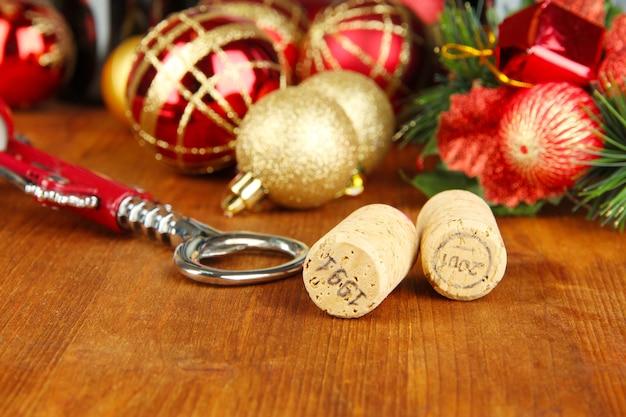 Tappi del vino con i giocattoli del nuovo anno sul primo piano del tavolo di legno