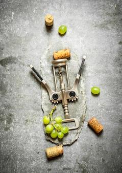 Cavatappi da vino con uva e tappi. sul tavolo di pietra.