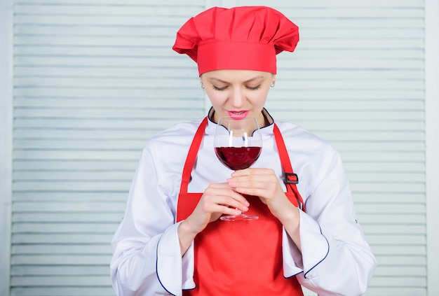 Degustazione di vini. quale vino servire a cena. come abbinare vino e cibo da esperto. la ragazza indossa il cappello e il grembiule per godersi l'aroma della bevanda. lo chef donna tiene un bicchiere di vino. squisito concetto di cena.