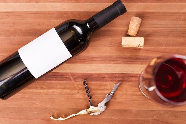 Il vino nei dettagli. vista dall'alto di bottiglia e bicchiere di vino con vino rosso sul tavolo di legno