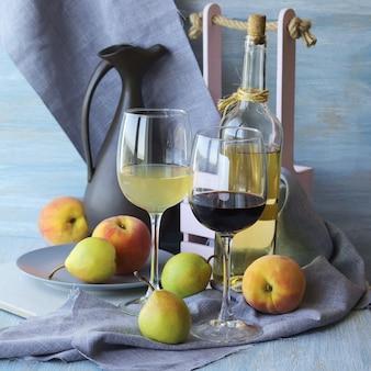 Vino e frutta su un tavolo di legno, tovagliolo di lino grigio, cucina casalinga