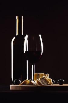 Bicchiere di vino e bottiglia, formaggio con muffa e uva su sfondo nero