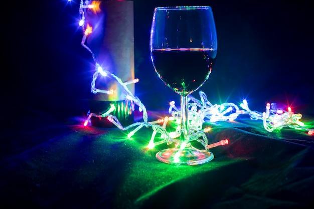 Bicchiere di vino e bottiglia in brillante ghirlanda bokeh su sfondo nero. avvicinamento