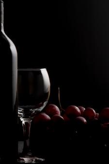 Bicchiere di vino, bottiglia di vino con e uva rossa su un buio.