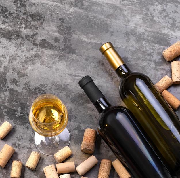 Bicchiere da vino, bottiglie e tappi di sughero sul piano del tavolo wiev