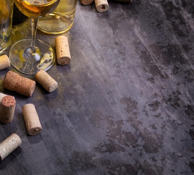 Bicchiere da vino, bottiglie e tappi di sughero sul tavolo di legno