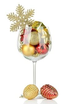 Bicchiere di vino pieno di decorazioni natalizie, isolato su bianco