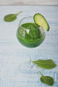 Bicchiere di vino riempito con spinaci verdi freschi e frullato di cetriolo su fondo di legno azzurro. bevande analcoliche. cibo sano e concetto vegetariano.