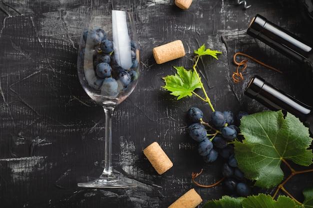 Bicchiere di vino pieno di uva all'interno. bottiglie di vino, grappoli d'uva con foglie e viti tappi per vino su fondo di cemento rustico scuro. composizione piatta del vino sul tavolo di pietra nera.