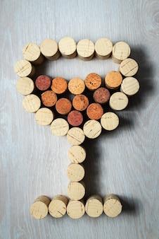 Bicchiere da vino fatto di tappi per vino su uno sfondo chiaro in legno