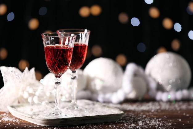 Bicchieri da vino con decorazioni natalizie sul tavolo innevato, primo piano
