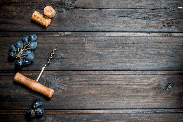 Vino. uva con cavatappi e tappi in legno.