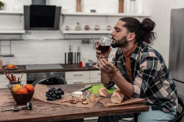 Amante del vino. piacevole giovane che si gode il suo vino rosso mentre è seduto in cucina