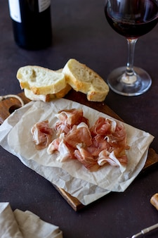 Merenda al vino. prosciutto, baguette. antipasti. antipasto di vino.