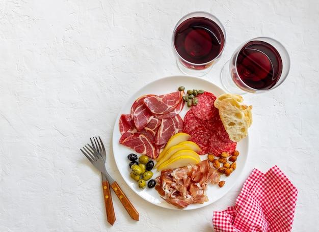 Merenda al vino. prosciutto di parma, prosciutto crudo, salame, mandorle, olive, baguette. antipasti.