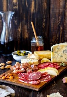 Merenda al vino. prosciutto di parma, prosciutto di parma, salame, mandorle, olive, baguette, gorgonzola, parmigiano. antipasti.