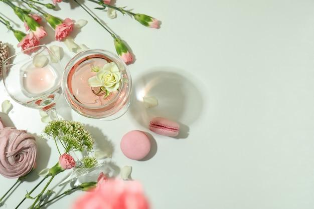 Vino, dolci e fiori sulla tavola bianca