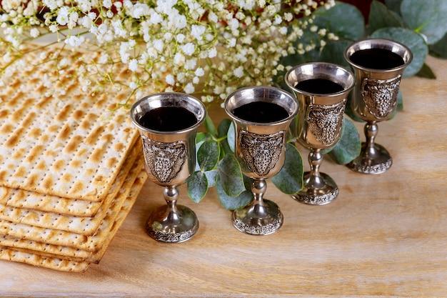 Vino kosher con quattro bicchieri di matzah a haggadah pasquale su un tavolo di legno vintage