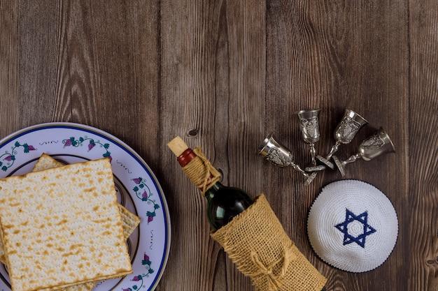 Vino kosher con quattro bicchieri di matzah a haggadah pasquale Foto Premium