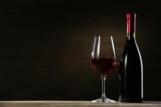 Bicchiere di vino e bottiglia su fondo in legno